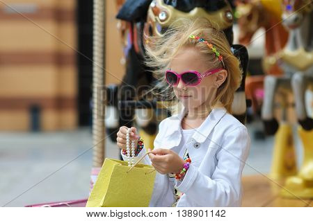 Child On Old French carousel in a holiday park. Elegant Charming cute little girl in fashionable clothes and sunglasses enjoys sitting with full shopping bags. Reviewing purchases on city street.