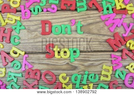 Don't Stop word on wooden table