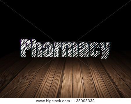 Medicine concept: Glowing text Pharmacy in grunge dark room with Wooden Floor, black background