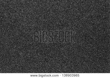 Black grainy plastic texture background, close up