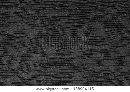 Black embossed plastic texture background, close up