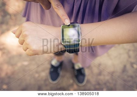 High angle view of female forefinger pressing the button on smart watch.