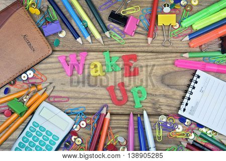 Wake up word and office tools on wooden table
