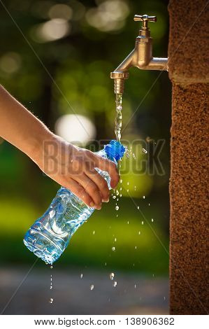 Close up of female hand pouring water in plastic bottle on faucet outdoors. Nature, summer and healthy lifestyle concepts.