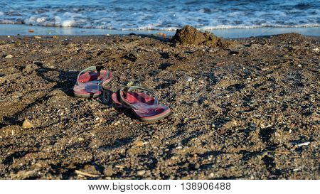 A pair of red sandal on a beach