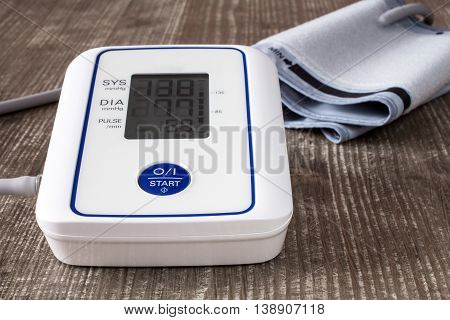 Digital blood pressure monitor on wooden table