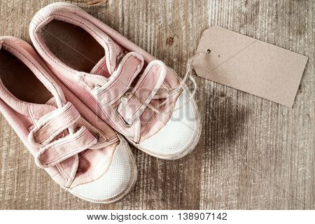 Kids shoes with blank tag on a wooden background