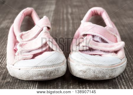 A pair of old pink sneakers on wooden surface