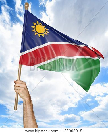 Person's hand holding the Namibian national flag and waving it in the sky, 3D rendering