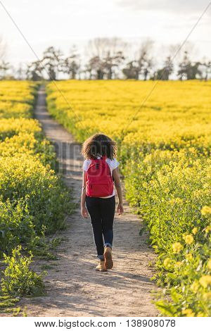 Beautiful happy mixed race African American girl teenager female young woman hiking with red rucksack in yellow field in golden evening sunshine