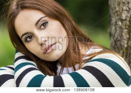 Outdoor portrait of beautiful thoughtful sad girl or young woman with red hair wearing a stripey jumper sitting & leaning against a tree in the countryside
