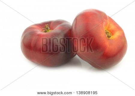 two fresh wild flat nectarines on a white background