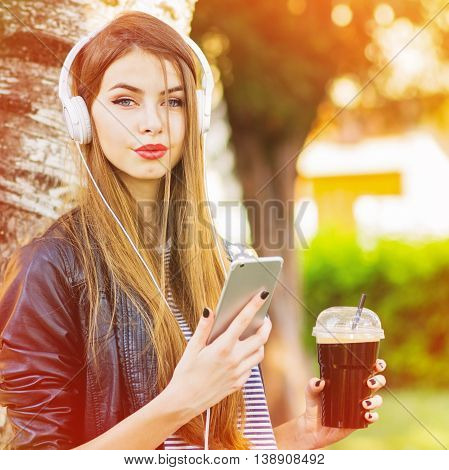 Beautiful young woman with smart phone, headphones and takeaway coffee outdoors in park on sunny day. Square format, medium retouch, vibrant colors.