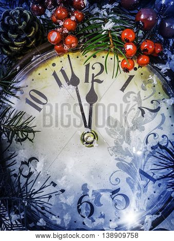 Christmas Eve and New Years at midnight. Clock covered with snow at cold blue tones.