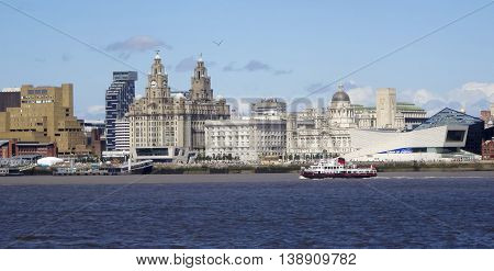 LIVERPOOL, ENGLAND, JULY 3. Pier Head from across the Mersey River on July 3, 2016, in Liverpool, England. Liverpool landmarks include The Royal Liver Building Merseyside Cunard Building Port of Liverpool Building George's Landing Stage Unity Residential
