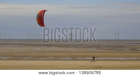 WALLASEY, ENGLAND, JULY 3. A tidal flat on July 3, 2016, near Wallasey, England. A man skateboards across the tidal flat sand using a parasail near Wallasey England.