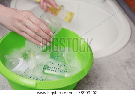 Woman hands washing baby bottles in plastic green basin