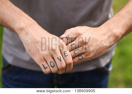 Man fists with fake tattoo