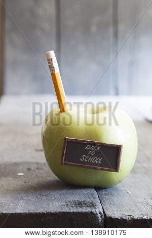 Back to school idea - text, yellow pencil and green apple on the table