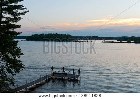 pier with people fishing as sun sets over steamboat bay and birch island of east gull lake in cass county minnesota outside brainerd baxter