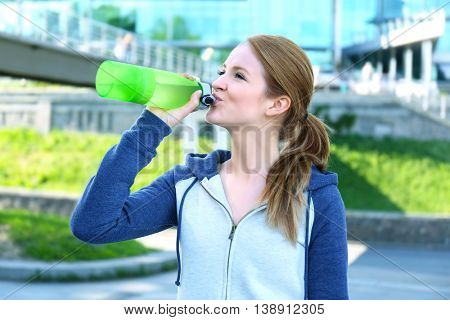 Sporty woman drinking water after jogging at park on a sunny day