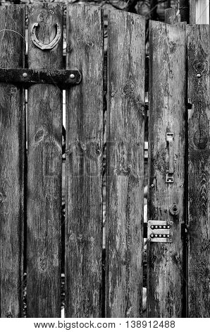 A wooden door with a horseshoe and electronic lock