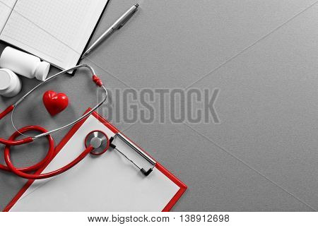 Red stethoscope with clipboard on grey table
