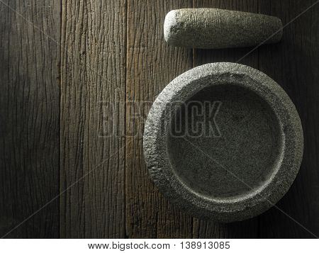top view of stone mortar and pestle on the wooden background