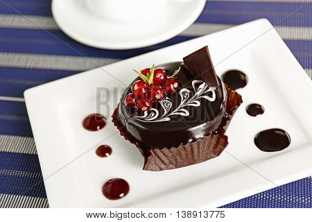 Chocolate cake with fresh currant on table