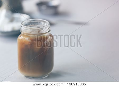 Iced coffee in glass jar on white wooden table