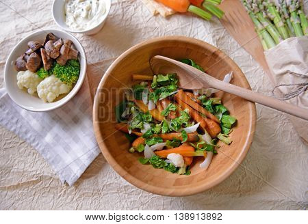 Fresh vegetable salad with baby carrot in wooden bowl, top view