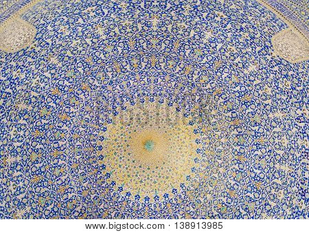 ISFAHAN, IRAN - OCT 14, 2014: Colors of patterned dome inside the ancient persian mosque on October 14, 2014. The 3rd largest city of Iran Isfahan is outstanding example of Iranian Islamic culture