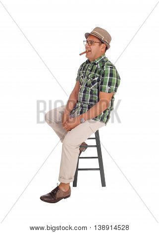 A middle age Hispanic man sitting on a chair and smoking his big cigar wearing a beige hat isolated for white background.