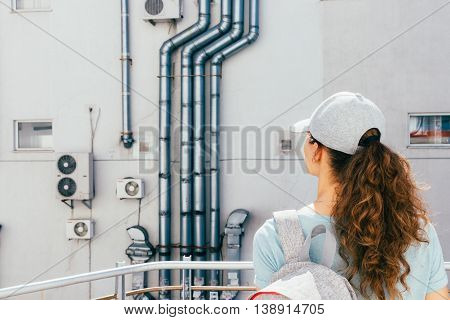 Young woman looks at the wall of the building with air conditioning and ventilation pipes