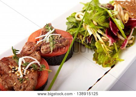 Beef medallions on tomato and grilled eggplant on a white plate