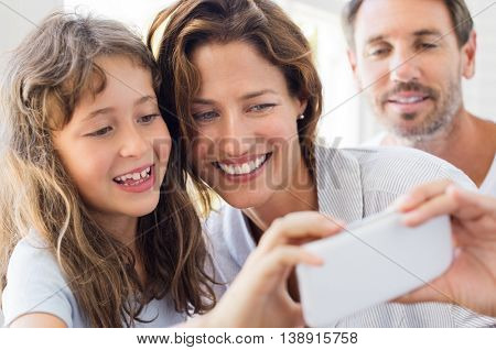 Smiling mother and daughter posing together to take a selfie. Father watching mother and daughter taking selfie at home. Happy family with one child taking a photo at home.