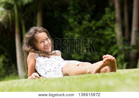 Smiling little girl lying on green grass. Cute girl lying down and enjoying leisure and vacation. Happy smiling girl sitting barefoot on green grass in the park and thinking.