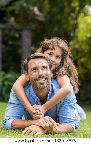 Young father and daughter lying on green grass. Happy daughter sitting on father back and smiling. Young little girl making a human pyramid with her dad and looking up.