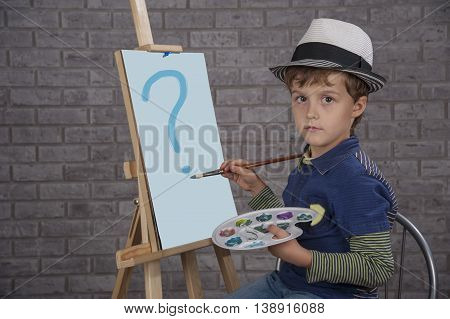 Boy in a white hat in the studio drawing sailing ship as an artist.