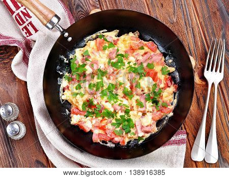 Scrambled eggs with ham, tomato and parsley