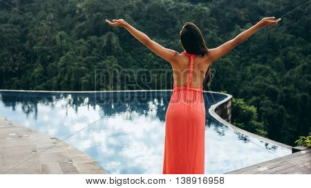 Young Woman Standing By A Swimming Pool
