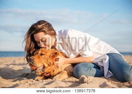 Cute lovely young woman hugging and playing ball with dog on the beach