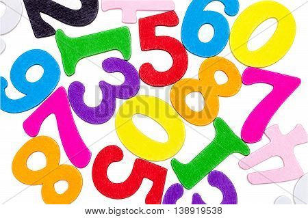 Wooden colorful numbers close-up scattered on a white background