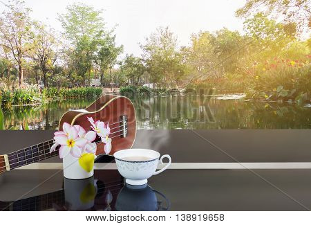 Cup Of Hot Tea Or Hot Drink With Flowers And Ukulele In Fresh Nature View