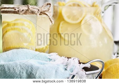 Lemonade in mason jars with extreme shallow depth of field. Fresh lemons and pitcher of fresh juice in background.
