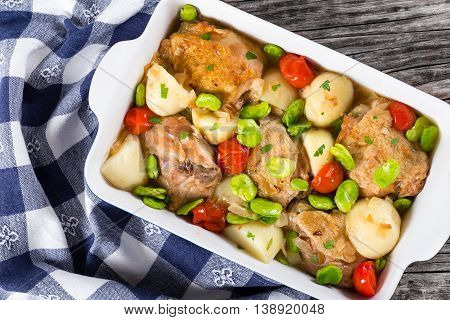 oven baked chicken things new potatoes tomatoes and butter lima bean in gratin dish on old wooden table with kitchen towel view from above