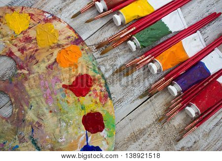 Brushes, paint, palette on wood background. Place for text.