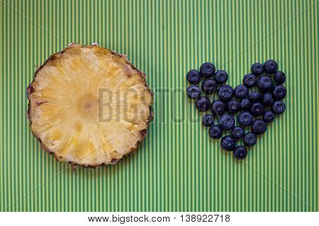 Round slice of fresh pineapple and blueberries arranged in heart shape on yellow and green stripe background