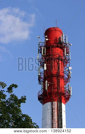 Red and white tube boiler with cables of telecommunications equipment primarily for cellular transmission