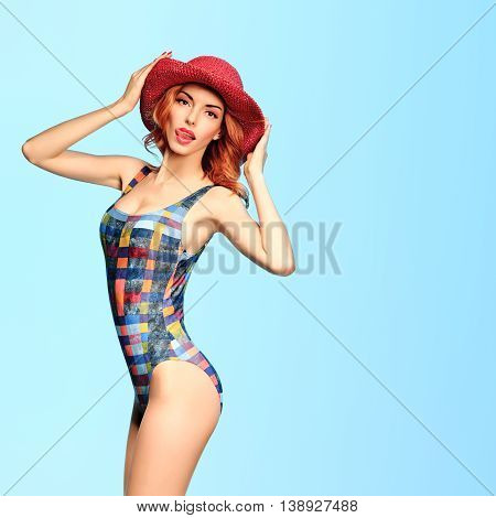 Fashion. PinUp woman in fashion Beach swimsuit. Playful Sexy Redhead Model girl, Summer Stylish Outfit, Hat licking lips. Beach body, sexy Trendy swimsuit, Pinup fashion.Summer holiday, Unusual Creative